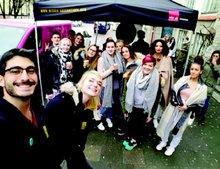 Jugendliche machen Selfie vorm Kampagnenbus der Besser-Abschneiden-Kampagne