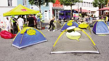 Aktion der ver.di Jugend für bezahlbare Wohnungen. Mehrere Zelte mit Sprechblasen wurden auf einem öffentlichen Platz aufgestellt.