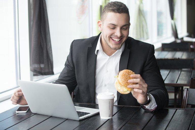 Mann mit Burger am Arbeitsplatz